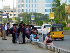 On attend le bus sur la chaussée. Si bien, les véhicules roulent également sur les trottoirs qui n'en sont peut-être pas.