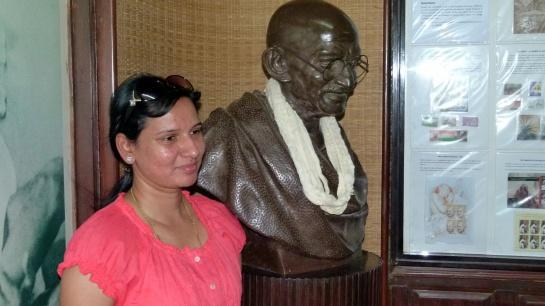 Les admirateurs de Gandhi se font photographier près de son buste dans l'entrée de la maison.